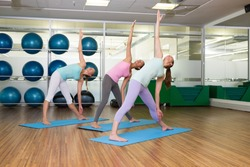 Yoga class in extended traingle position in fitness studio at the leisure center