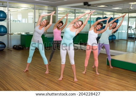 Yoga class in tree pose in fitness studio at the leisure center