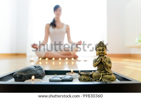 Yoga concept indoor. Woman meditating in lotus pose with buddha and candles on foreground.
