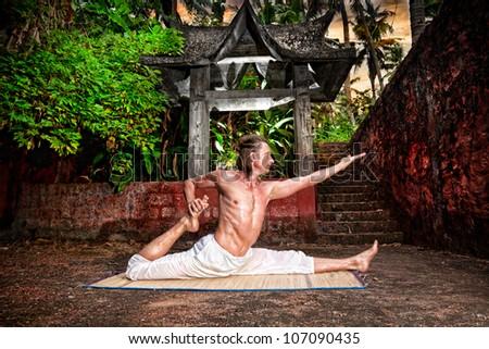 yoga eka pada raja kapotasanafit man in white trousers