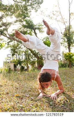 Yoga female master with perfect balance practices scorpion position