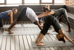 Yoga fitness instructor teacher helping african man beginner doing stretching downward facing dog exercise standing in adho mukha svanasana pose at studio group training class with multiracial people