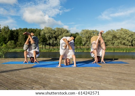 yoga, fitness, sport, and healthy lifestyle concept - group of people making tripod egg pose n mat outdoors on river or lake berth Foto stock ©
