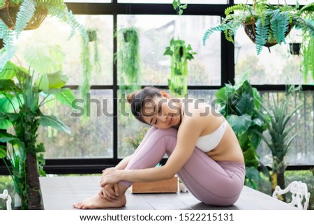 Yoga for relaxation and wellbeing concept. Young Asian healthy woman in sportswear sitting in glasshouse and happy with freshness of plants. Living with nature good and give pleasure to people.