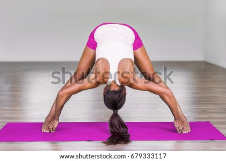 Yoga girl doing wide leg forward fold at gym. Woman stretching legs muscles doing Prasarita Padottanasana training stretches on exercise mat in fitness class.