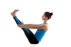 Yoga girl practices Boat Pose (Paripurna Navasana) in black and blue sportswear on white background
