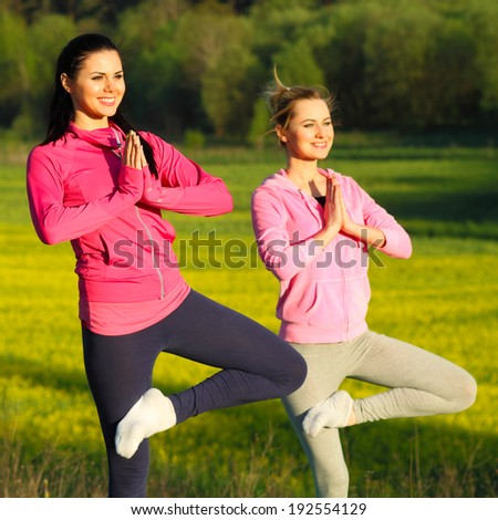 yoga Girls on the background field of yellow flowers. yoga instructor shows poses