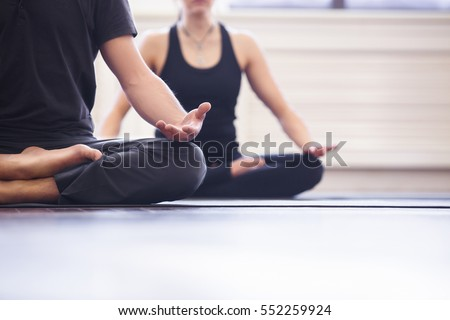Yoga group concept. Young couple meditating together, sitting back to back on windows background, copy space