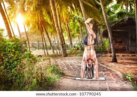 Yoga handstand pose with legs in garudasana by fit man with dreadlocks on the beach near the fishermen hut in Varkala, Kerala, India