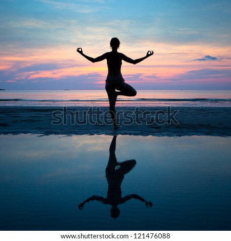 Yoga, harmony of health (silhouette young woman on the beach at sunset)