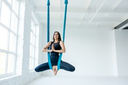 Yoga in a white gym. Gymnastics performs physical exercises fly-yoga, pilates, restorative