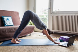 Yoga instructor or student in downward facing dog posture participating in online video lesson over the internet from home.