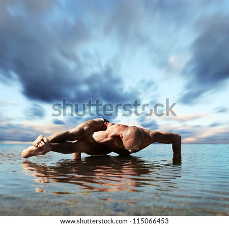 Yoga into the water. Man doing eight arcs twisted pose