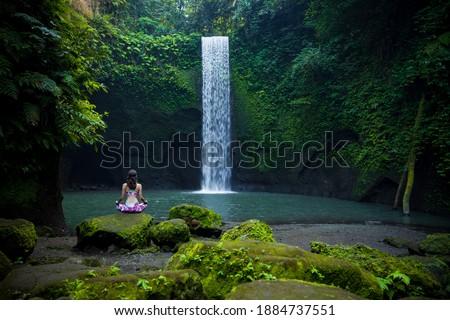 Yoga lotus pose. Young Caucasian woman sitting on the stone, meditating, practicing yoga, pranayama at waterfall. Hands in gyan mudra. Yoga retreat. View from back. Tibumana waterfall, Bali, Indonesia