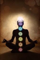 Yoga man in lotus pose with chakra symbols