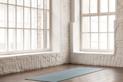 Yoga mat on natural wooden floor in empty room in fitness center, comfortable space for doing sport exercises, big windows and white brick walls, modern yoga class room with nobody