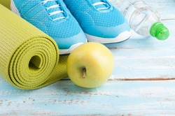 Yoga mat, sport shoes, apple, bottle of water on blue wooden background. Concept healthy lifestyle, healthy food, sport and diet. Sport equipment. Selective focus
