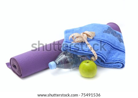 Yoga mat, towel bottle of water, measurement tape and apple isolated on white background.