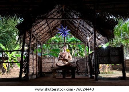 Yoga meditation in lotus pose by Caucasian man in yoga hall at banana trees background in Varkala, Kerala, India