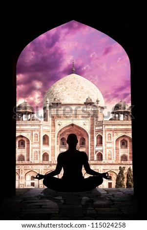 Yoga meditation in lotus pose by man silhouette in arch at Humayuns tomb and purple sky background in New Delhi, India