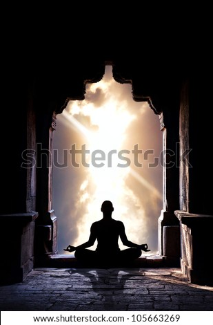 Yoga meditation in lotus pose by man silhouette in old temple arch at dramatic sky background. Free space for text - stock photo