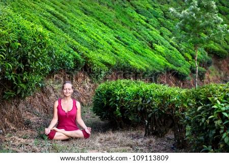 Yoga meditation in padmasana lotus pose by woman in red cloth on tea plantations in Munnar hills, Kerala, India