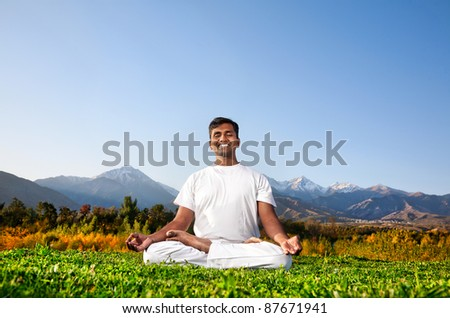 Yoga meditation in padmasana pose by happy Indian Man in white cloth in the morning at mountain background. Free space for text