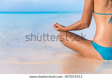 Yoga meditation on beach. Bikini body woman meditating relaxing sitting in water in tropical summer travel. Closeup on hand. Health and fitness retreat concept.