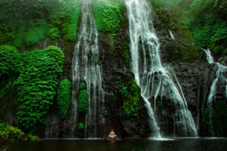 Yoga meditation on green tropical waterfall on Bali. Huge powerful water with small person under. Open chakra heal meditate concept