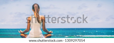 Yoga meditation wellness woman meditating on morning sunrise beach background in peace and zen positive attitude panoramic banner. Active sport and fitness lifestyle image.