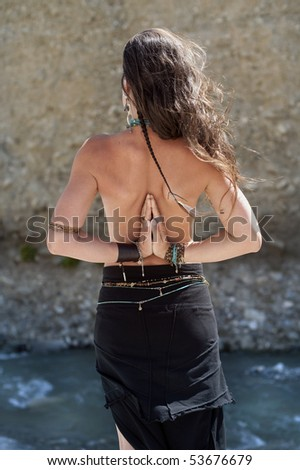 Yoga nature spa. The back of a beautiful woman with her hands in namaste.