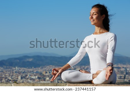 Yoga on high altitude with big city on background, smiling woman seated in yoga pose on amazing city background, woman meditating yoga and enjoying sunny evening, woman makes yoga on mountain hill