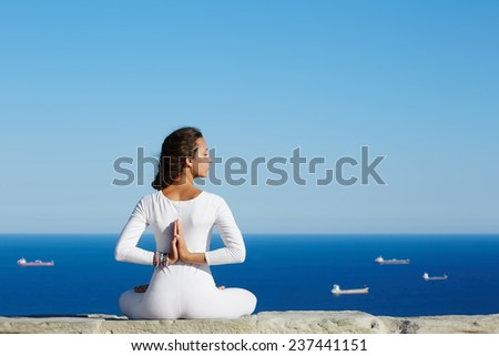 Yoga on high altitude with sea with ships on background, woman seated in yoga pose on amazing sea background, woman meditating yoga enjoying sunny evening, woman makes yoga meditation on mountain hill