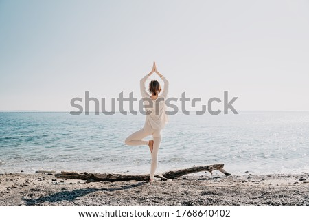 Yoga on the beach. Woman practicing yoga on coastline of the ocean. Beautiful girl relaxing by the sea. Calm, serene, minimalist photo with copy space. Healthy active lifestyle, vitality, zen. Foto d'archivio ©