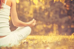Yoga outdoors in warm autumn park. Woman sits in lotus position zen gesturing. Concept of healthy lifestyle and relaxation