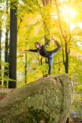 Yoga outdoors - sporty fit woman doing asana Narajasana in autumn park on the big boulder