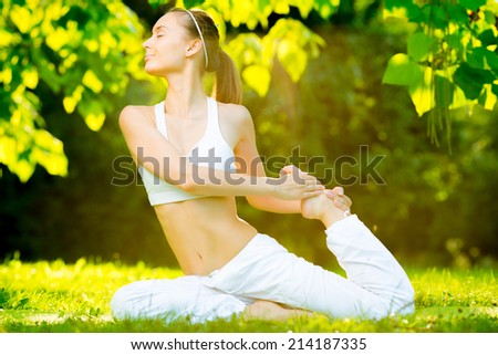 Yoga outdoors. Young healthy beautiful woman is doing a yoga asana in the green park. Concept of healthy lifestyle and relaxation
