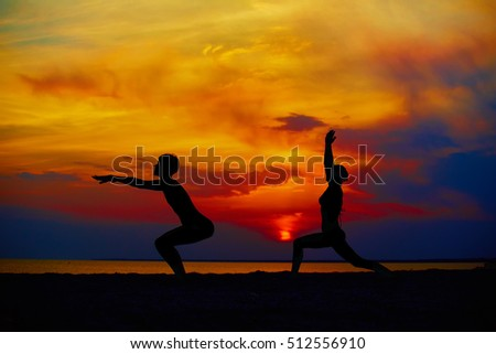Stock Photo Yoga people training and meditating in warrior pose outside by beach at sunrise or sunset.