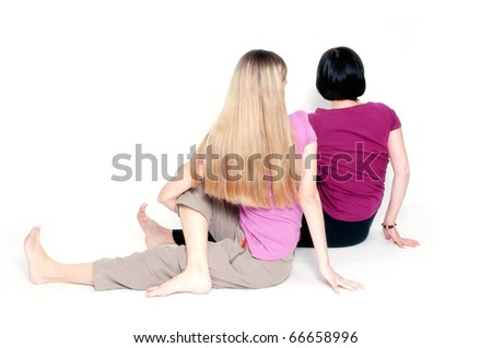 """Yoga pose called """"sitting half spinal twist"""" by young and aged woman."""