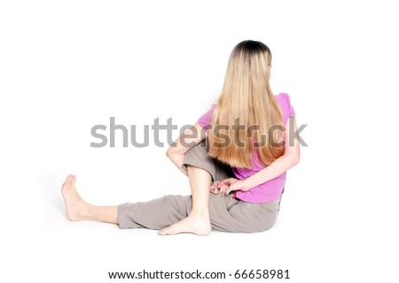 """Yoga pose called """"sitting half spinal twist"""" by young woman."""