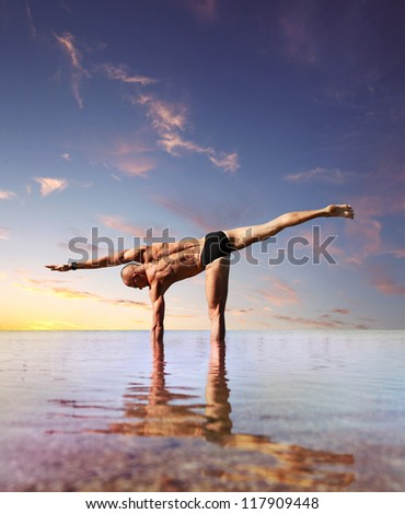 Yoga practice. Man doing lateral stretching yoga exercise standing into the water