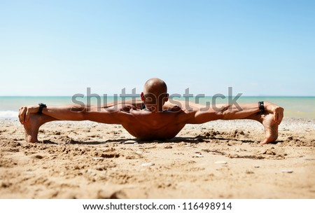 Yoga practice. Man in strong stretching yoga pose on the sea beach