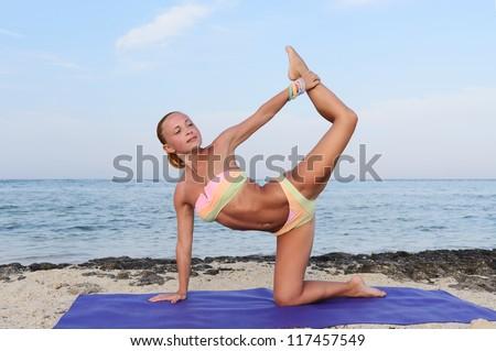 Yoga practice. Slim woman practicing yoga asana by the sea
