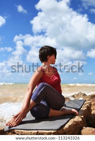 Yoga practice. Woman in half spinal twist yoga pose
