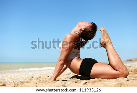 Yoga practice. Young flexible woman doing full cobra yoga pose at the beach