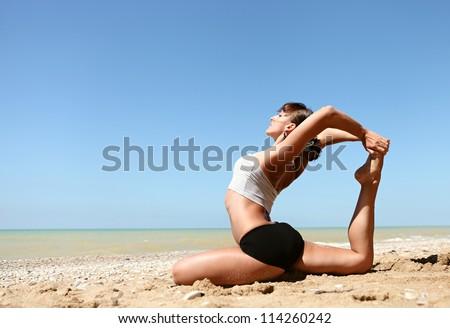 Yoga practice. Young girl doing king pigeon yoga pose on the beach