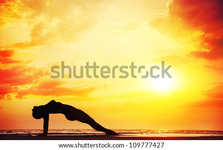Yoga purvottasana upward plank pose by beautiful woman on the beach near the ocean at dramatic sunset background