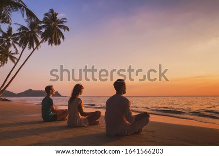 yoga retreat on the beach at sunset, silhouettes of group of people meditating Stok fotoğraf ©