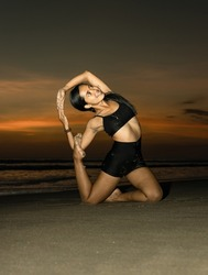 Yoga retreat. Slim Asian woman practicing Eka Pada Rajakapotasana. Mermaid Pose. Pigeon variation. Hip opener, heart-opener, backbend. Fit body. Sunset beach yoga. Seminyak beach, Bali, Indonesia