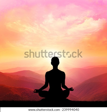 Yoga silhouette on the mountain in the rays of the dawn sun #239994040